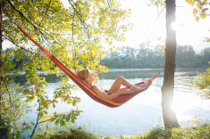 stock-photo-47336226-serene-woman-on-hammock-by-the-river-enjoying-nature